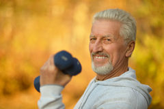 Elderly man exercising with dumbbells Stock Photography