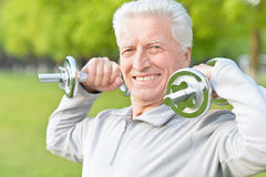 Elderly man exercising with dumbbells Royalty Free Stock Images