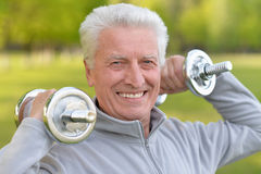 Elderly man exercising with dumbbells Stock Image