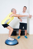 Elderly man exercising with  personal trainer Stock Photos
