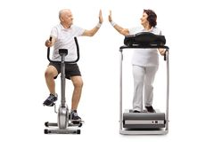 Elderly man exercising on a stationary bike and an elderly woman. Elderly men exercising on a stationary bike and an elderly women on a treadmill high-fiving Royalty Free Stock Photography