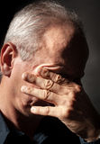 Elderly man with face closed by hand Royalty Free Stock Photo