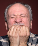 Elderly man with face closed by hands Stock Images