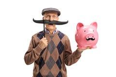Elderly man with fake moustache holding a piggybank. With fake moustache isolated on white background Stock Photo