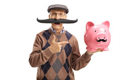 Elderly man with fake moustache pointing at a piggybank. With fake moustache isolated on white background Royalty Free Stock Photo