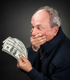 Elderly man with fan of dollars Royalty Free Stock Photo
