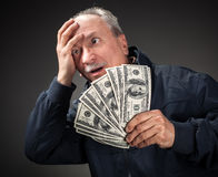 Elderly man with fan of dollars Royalty Free Stock Image