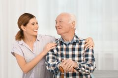 Elderly man with female caregiver. At home stock photos