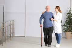 Elderly man with female caregiver indoors. Space for text royalty free stock images