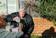 Elderly man filling bird feeder with peanuts. Royalty Free Stock Photos
