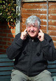 Elderly man with fingers in his ears. Royalty Free Stock Photography