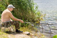 Elderly man fishing on a freshwater lake Royalty Free Stock Photos