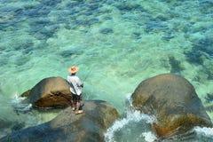 Elderly man fishing in the sea Royalty Free Stock Photo
