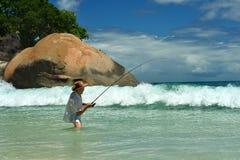 Elderly man fishing in the sea Royalty Free Stock Image