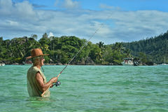 Elderly man fishing in the sea Stock Photography