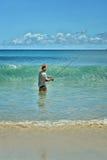 Elderly man fishing in the sea Stock Photos