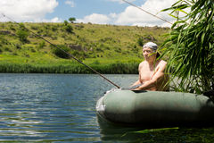 Elderly man fishing shirtless on a tranquil lake. As e sits in a rubber dinghy with his rod and reel waiting patiently for a bite stock photography