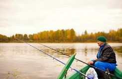 Elderly man fishing on a tranquil lake sits in wooden rod with his rod Stock Photos
