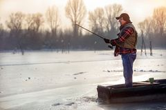 Elderly man fishing in the winter. On the lake royalty free stock photo
