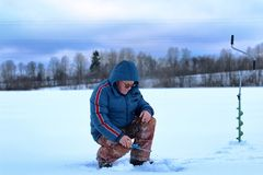 Elderly man fishing in the winter on the lake Stock Image