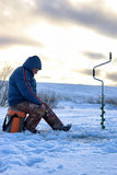 Elderly man fishing in the winter on the lake Stock Images