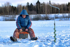 Elderly man fishing in the winter on the lake Royalty Free Stock Photography