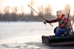 Elderly man fishing in the winter on the lake. Elderly man fishing in the winter on the frozen lake stock photo