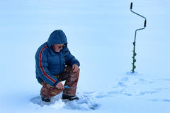Elderly man fishing in the winter on the lake Stock Photo