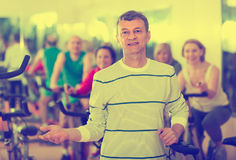 Elderly man on fitness cycle in fitness club Stock Image