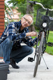Elderly man fixing bicycle royalty free stock photography