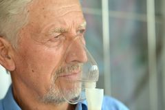 Elderly man with flu inhalation Royalty Free Stock Images