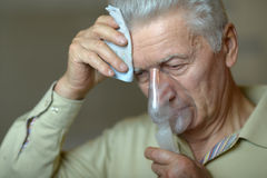 Elderly man with flu inhalation Royalty Free Stock Photos