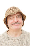 Elderly man in a funny hat with suspicion and disdain looking at Royalty Free Stock Photography