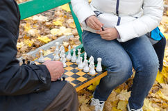 Elderly man a game of chess with woman sit together on a wooden park bench. Close up of the hands of an elderly men making a chess move he sits playing  game on Royalty Free Stock Photo