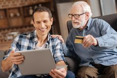 Elderly man giving bank card to son doing online shopping Stock Photography