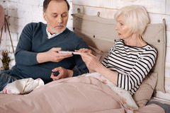 Elderly man giving pills case to his ill wife. It will help. Senior handsome men is giving pills case to his elderly sick wife lying on bed covered with warm Royalty Free Stock Images