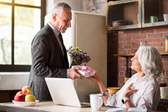 Elderly man giving present and flowers to his happy wife. Surprise. Retired couple at the kitchen of their house celebrating lady's birthday Stock Images