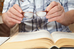 An elderly man with glasses reading a book Stock Image