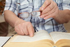An elderly man with glasses reading a book Stock Photography