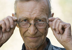 Elderly the man in glasses. Smiling elderly the man, holding with hands glasses Royalty Free Stock Photo