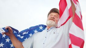 An elderly man with a gray beard holding a US flag on his shoulders. Patriotic day. A man in a cap celebrates US. Independence Day on July 4th stock footage