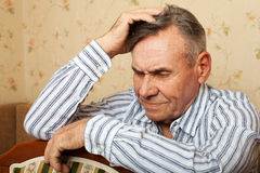 Elderly man grieves at home. Royalty Free Stock Image