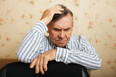 Elderly man grieves at home. Stock Image