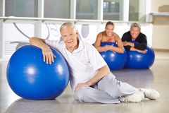 Elderly man with gym ball in health club. Elderly men exercising with gym ball in health club for rehab Royalty Free Stock Photography