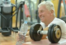 Elderly man in a gym. Drinking water after exercise Royalty Free Stock Photo
