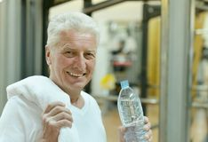 Elderly man in a gym. Drinking water after exercise Stock Photos