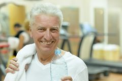 Elderly man in a gym. Drinking water after exercise Royalty Free Stock Images