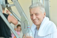Elderly man in a gym. Drinking water after exercise Stock Photo