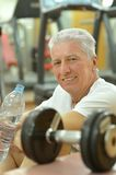 Elderly man in a gym. Exercising with dumbbells royalty free stock photo