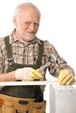 Elderly man hammering. Lloking up at camera, smiling, isolated on white royalty free stock image